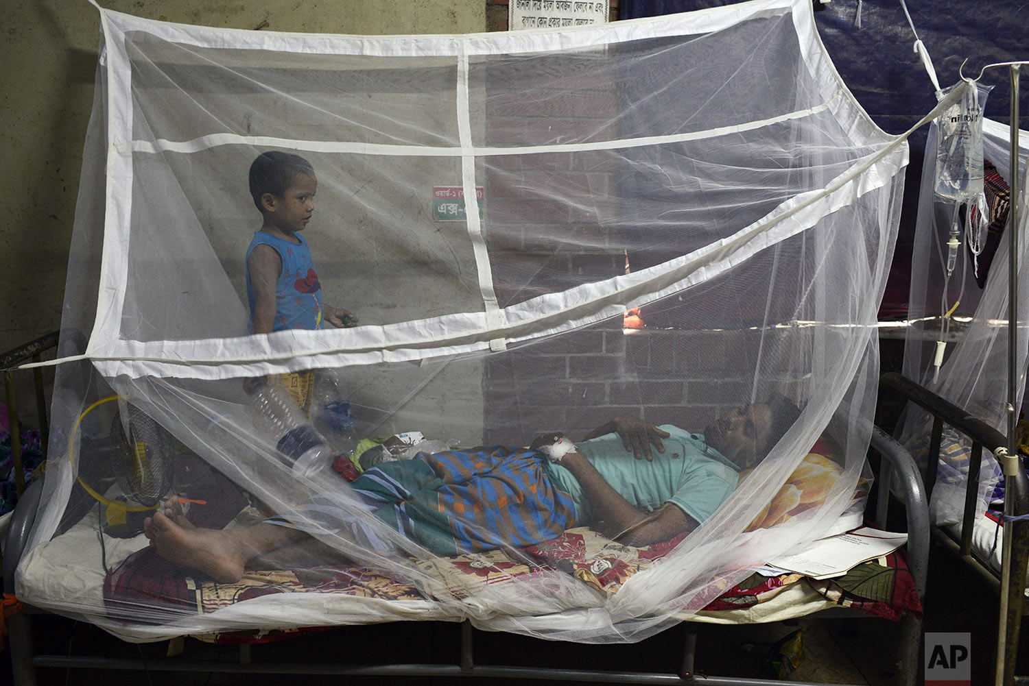 A man receives treatment for dengue, with his son standing beside him, at Shaheed Suhrawardy Medical College and Hospital in Dhaka, Bangladesh, Wednesday, July 31, 2019. (AP Photo/Mahmud Hossain Opu)