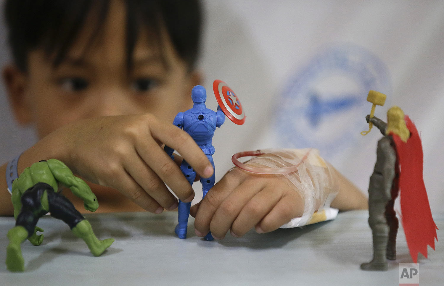 A young dengue patient plays with his action hero figurines inside his room at the San Lazaro government hospital in Manila, Philippines on Wednesday, Aug. 7, 2019. (AP Photo/Aaron Favila)