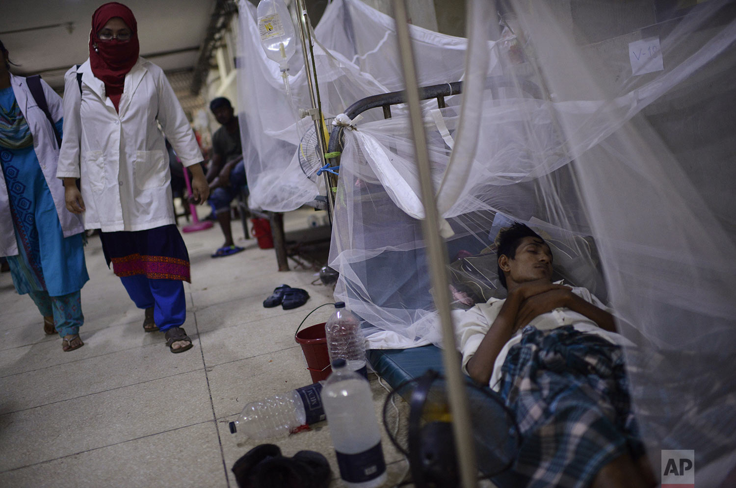 A medical officer walks past patients receiving treatment for dengue at Shaheed Suhrawardy Medical College and Hospital in Dhaka, Bangladesh, Wednesday, July 31, 2019. (AP Photo/Mahmud Hossain Opu)
