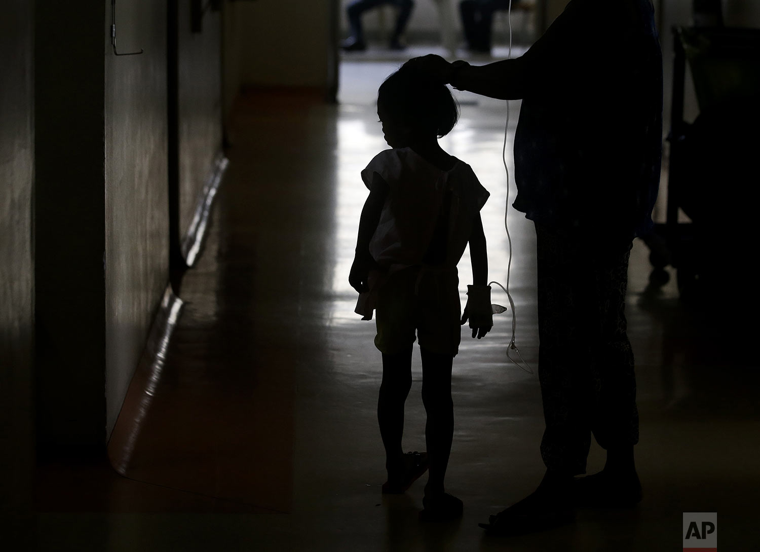 A young dengue patient walks inside the San Lazaro government hospital in Manila, Philippines on Wednesday, Aug. 7, 2019. (AP Photo/Aaron Favila)