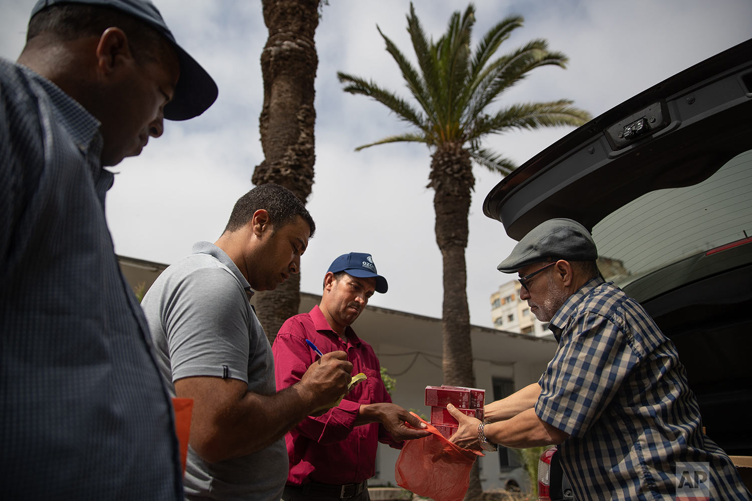 Habib El Ghazaoui, right, a father who runs the Association for Solidarity with Children of the Moon, distributes topical cream to parents of children affected by a rare disorder called xeroderma pigmentosum, or XP, inside a hospital in Casablanca, Morocco, July 24, 2019. (AP Photo/Mosa'ab Elshamy)