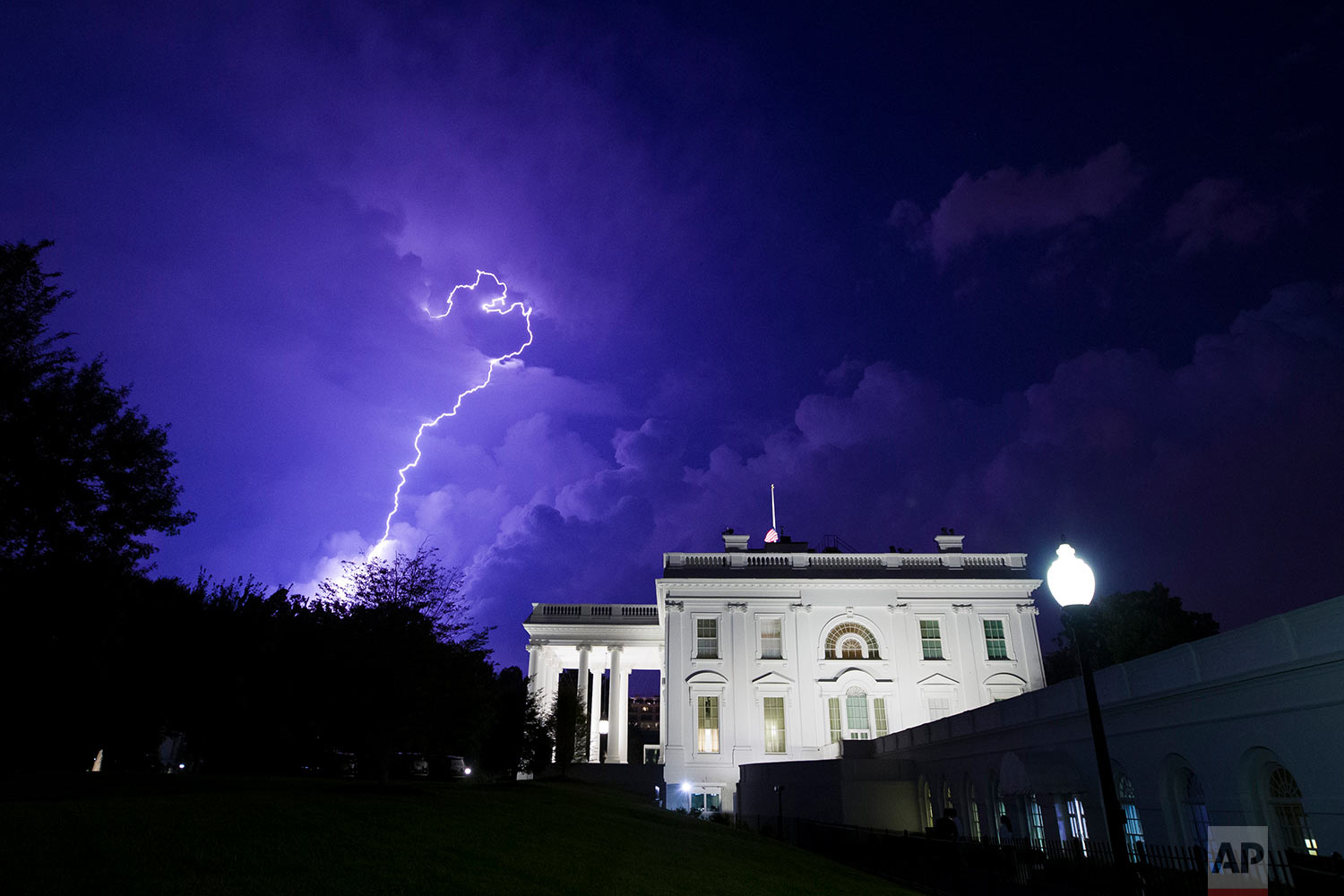 A bolt of lightning illuminates the clouds of a thunderstorm behind the White House, Tuesday, Aug. 6, 2019, in Washington. (AP Photo/Alex Brandon)