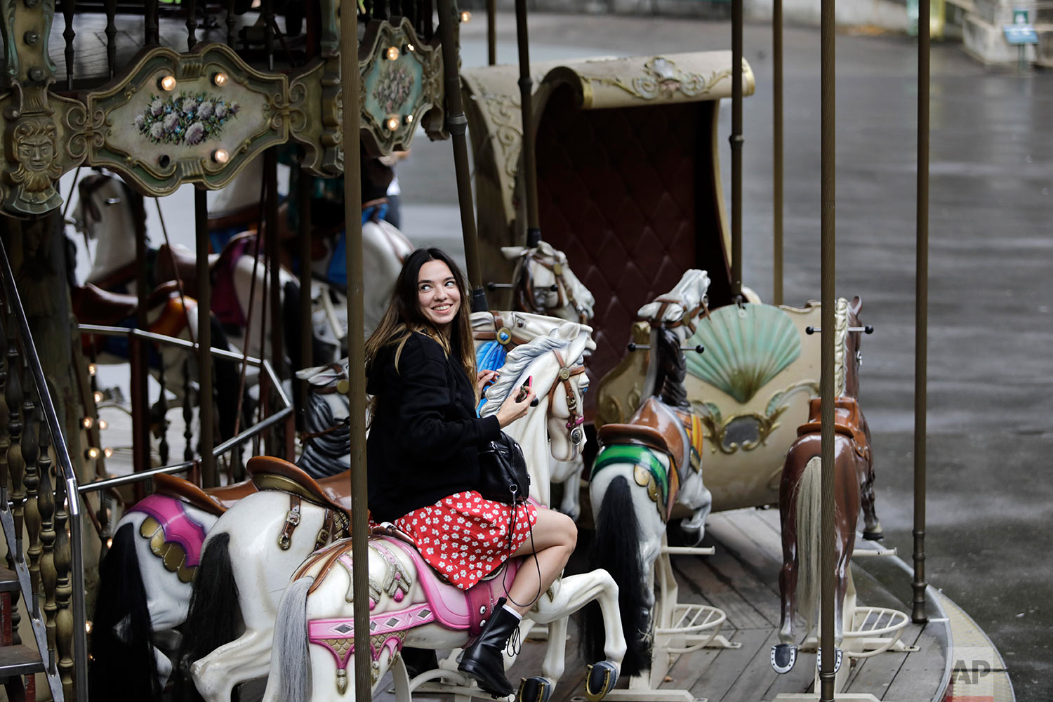 A woman smiles as she takes a ride on a carousel in the Montmartre district of Paris Friday, Aug. 9, 2019. (AP Photo/Lewis Joly)