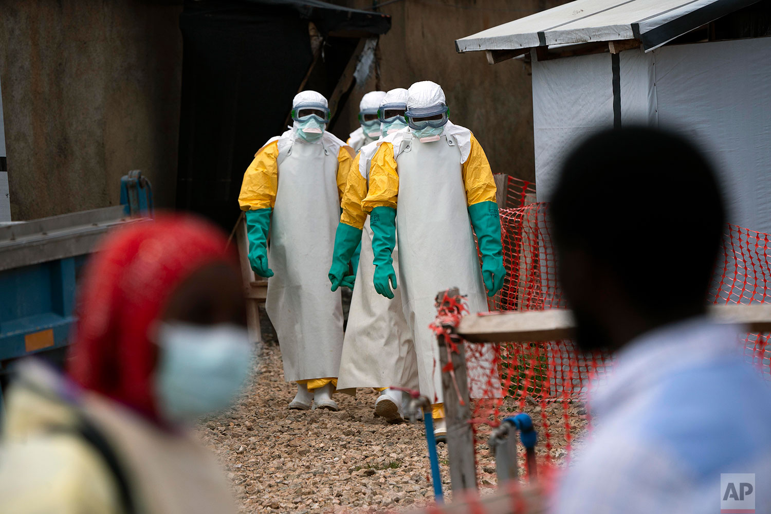In this July 16, 2019 photo, health workers dressed in protective gear begin their shift at an Ebola treatment center in Beni, Congo DRC.  (AP Photo/Jerome Delay)