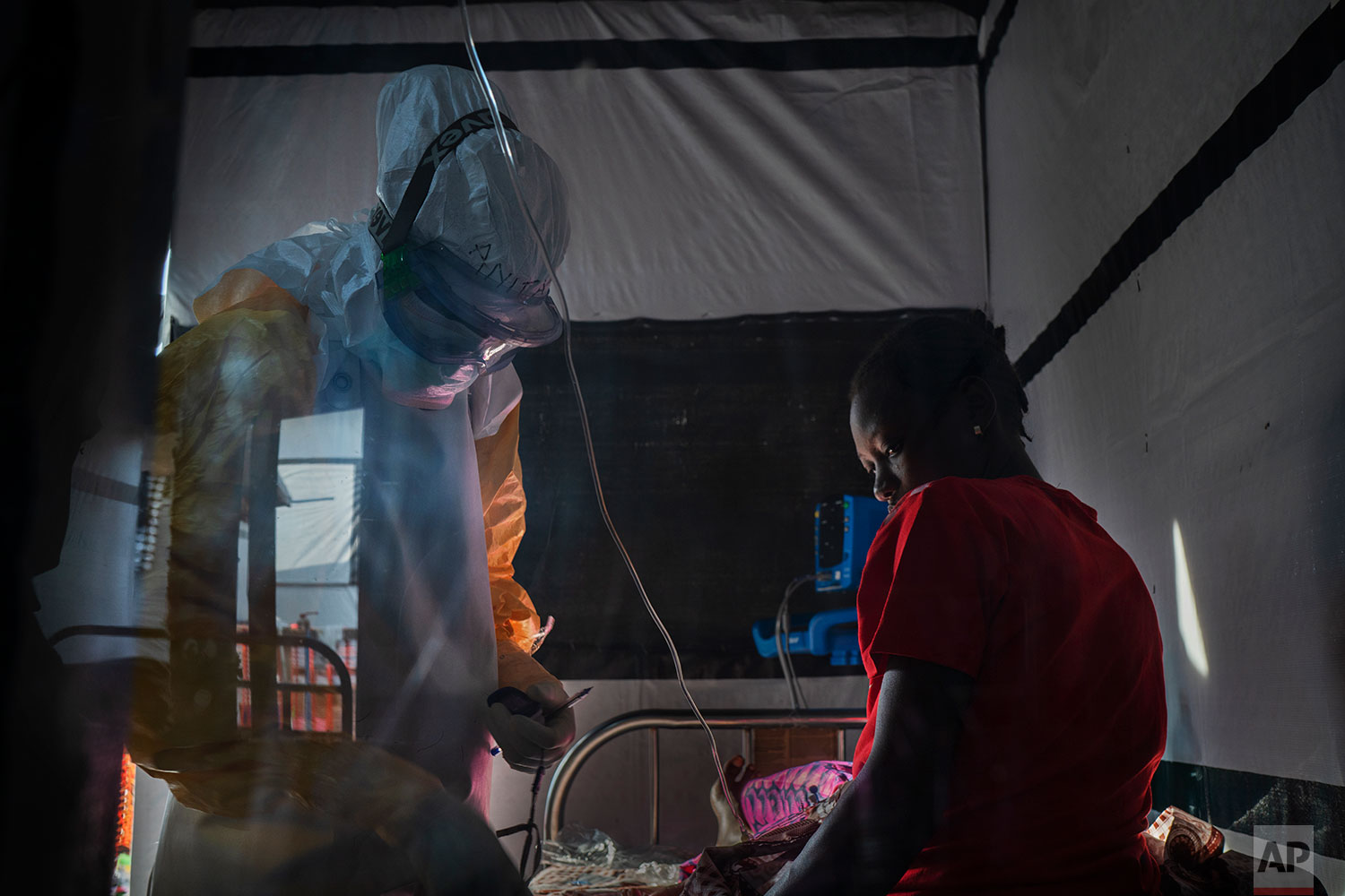 In this July 13, 2019 photo, health workers dressed in protective gear  check on Ivette Adania, 24, a mother of four whose husband died of Ebola, at an Ebola  treatment center  in Beni, Congo DRC.  (AP Photo/Jerome Delay)