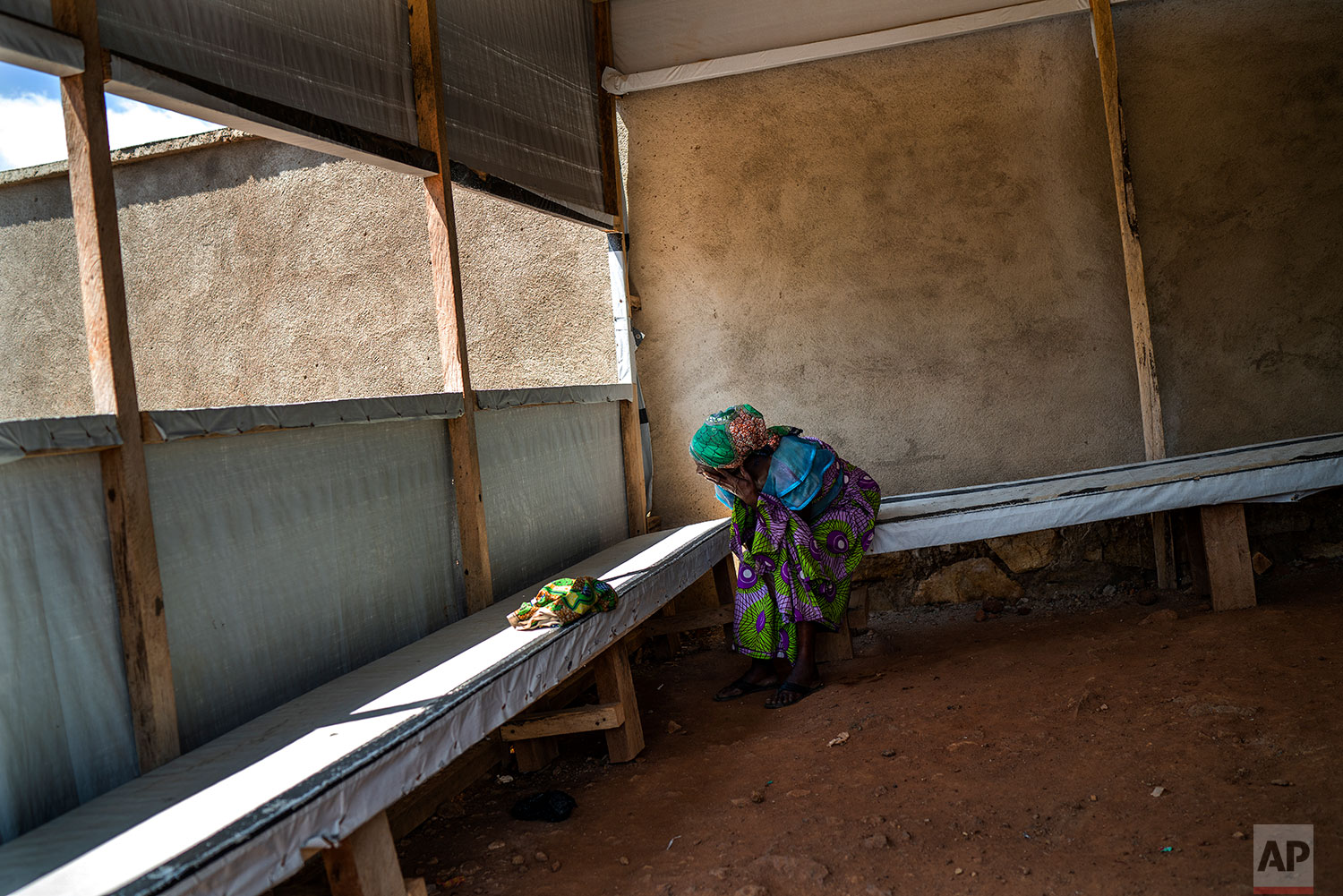 In this July 14, 2019 photo, a woman waits at the morgue for the body of her relative to be cleared for burial in Beni, Congo DRC. (AP Photo/Jerome Delay)