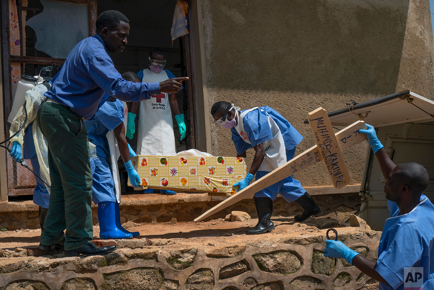 In this July 14, 2019 photo, Red Cross workers carry the remains of 16-month-old Muhindo Kakinire  rom the morgue into a truck as health workers disinfect the area in Beni, Congo DRC. (AP Photo/Jerome Delay)
