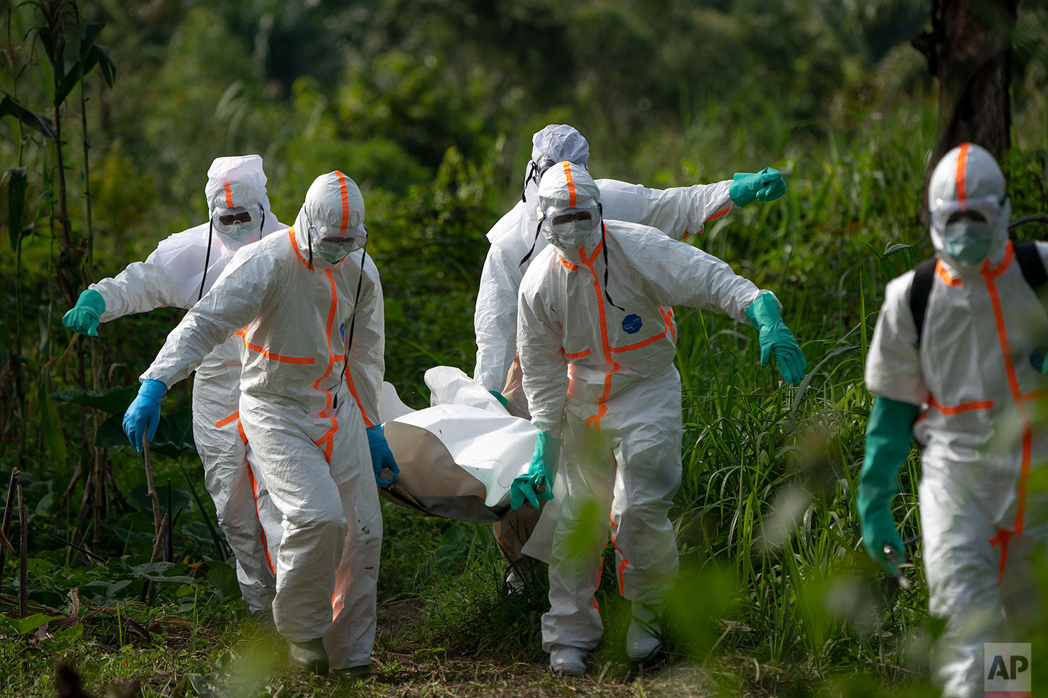 In this July 14, 2019 photo, burial workers dressed in protective gear  carry the remains of Mussa Kathembo, an Islamic  scholar who had prayed over those who were sick, and died of Ebola, in Beni, Congo DRC.  (AP Photo/Jerome Delay)