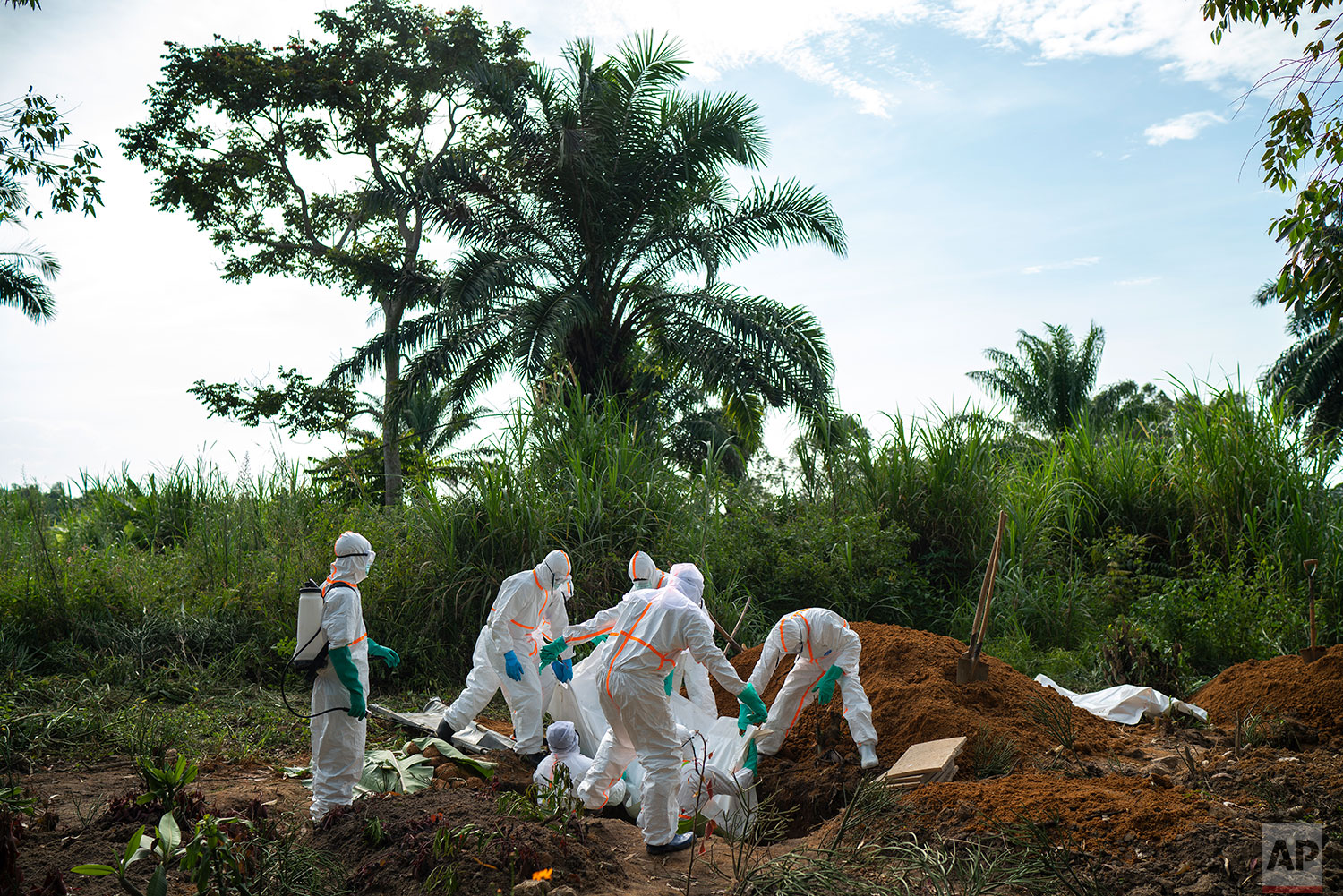 In this July 14, 2019 photo, burial workers  bury the remains of Mussa Kathembo, an Islamic scholar who had prayed over those who were sick in Beni, Congo DRC. Kathembo died of Ebola. (AP Photo/Jerome Delay)