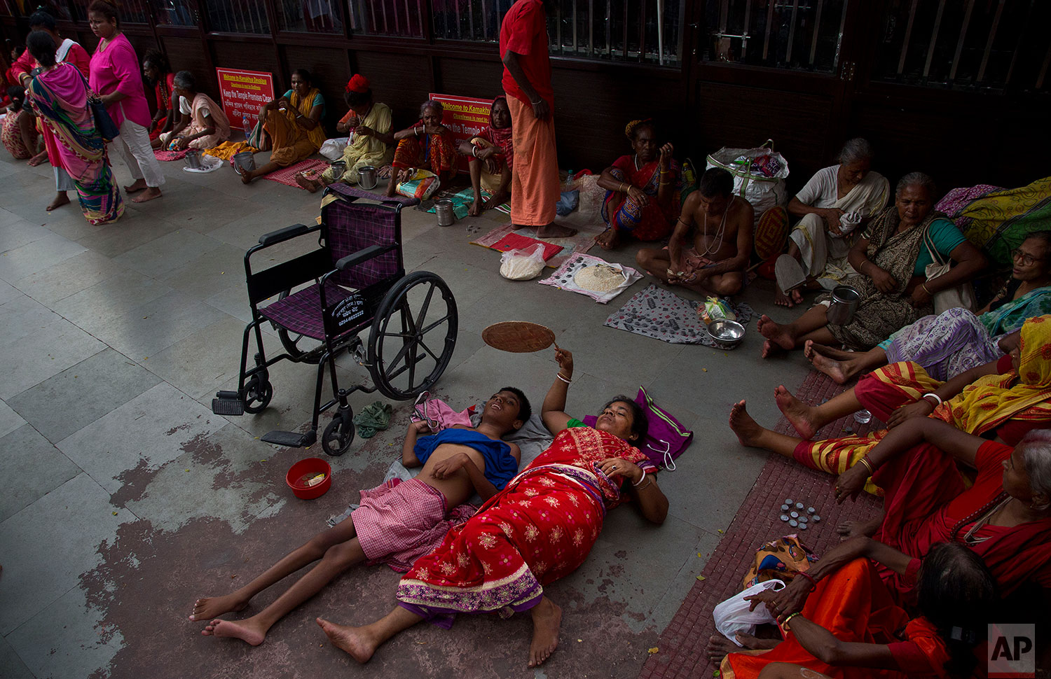 Monika Deb Nath, 45, uses a hand fan and rests on the floor with her son Gopal, 17, at the Kamakhya temple during the Ambubachi festival in Gauhati, India, June 25, 2019 . Monika, 45, and her husband have visited the Kamakhya temple four years in a row for the annual Ambubachi festival, praying for a miracle to heal their son from cerebral palsy, which has left him with almost no control over his own body. The temple is presided over by the goddess Kamakhya, the most important goddess of tantric worship, an esoteric form of Hinduism.(AP Photo/Anupam Nath)