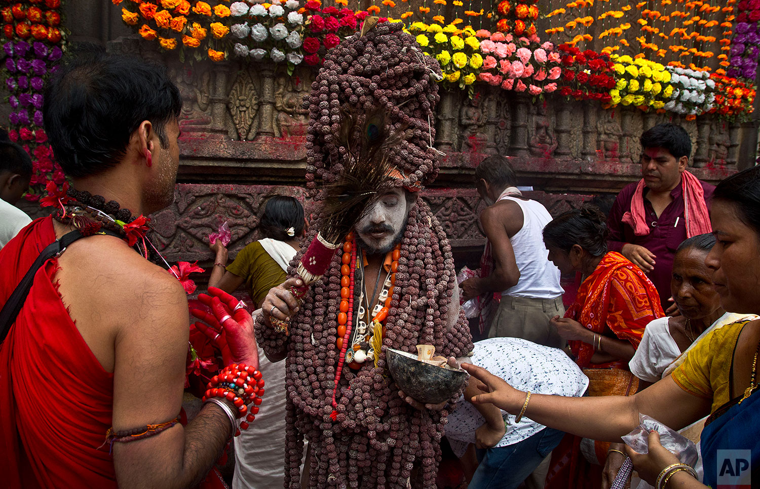 A Sadhu, or Hindu holy man, blesses devotees during Ambubachi festival at Kamakhya templein Gauhati, India, June 25, 2019 . The temple is presided over by the goddess Kamakhya, the most important goddess of tantric worship, an esoteric form of Hinduism. The four-day Ambubachi festival is a celebration of Kamakhya's yearly menstrual cycle, and it brings hundreds of thousands of devotees to the temple. (AP Photo/Anupam Nath)