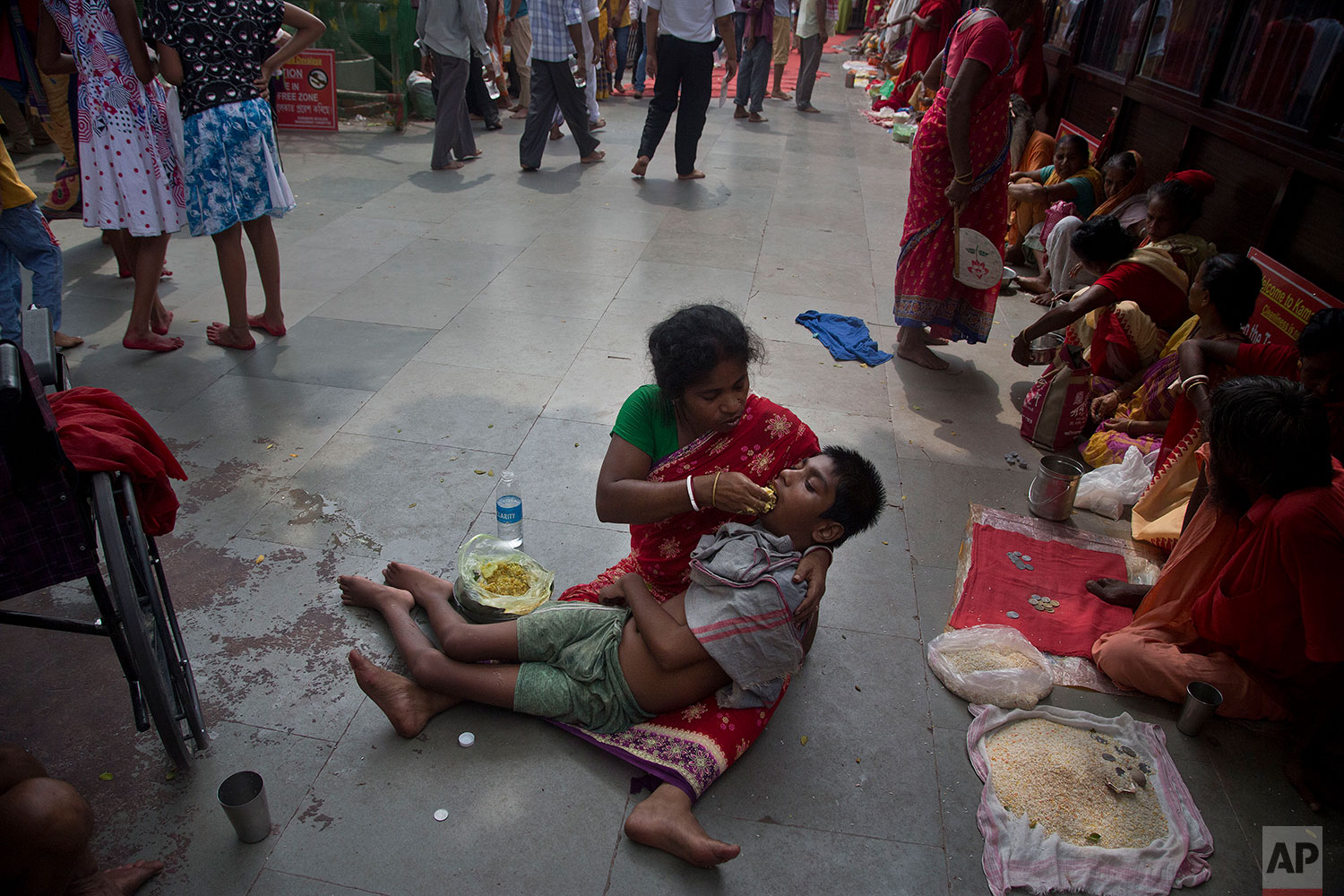 Monika Deb Nath, 45, feeds her son Gopal, 17, at the Kamakhya temple during the Ambubachi festival in Gauhati, India, June 25, 2019 . Monika, 45, and her husband have visited the Kamakhya temple four years in a row for the annual Ambubachi festival, praying for a miracle to heal their son from cerebral palsy, which has left him with almost no control over his own body. The temple is presided over by the goddess Kamakhya, the most important goddess of tantric worship, an esoteric form of Hinduism.(AP Photo/Anupam Nath)