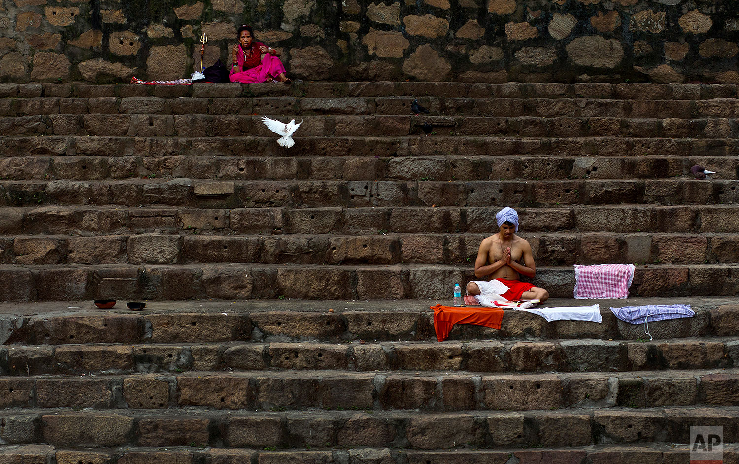 devotees perform rituals sitting on steps of the Kamakhya temple during the Ambubachi festival in Gauhati, India, June 25, 2019 .  The temple is presided over by the goddess Kamakhya, the most important goddess of tantric worship, an esoteric form of Hinduism. The four-day Ambubachi festival is a celebration of Kamakhya's yearly menstrual cycle, and it brings hundreds of thousands of devotees to the temple. (AP Photo/Anupam Nath)