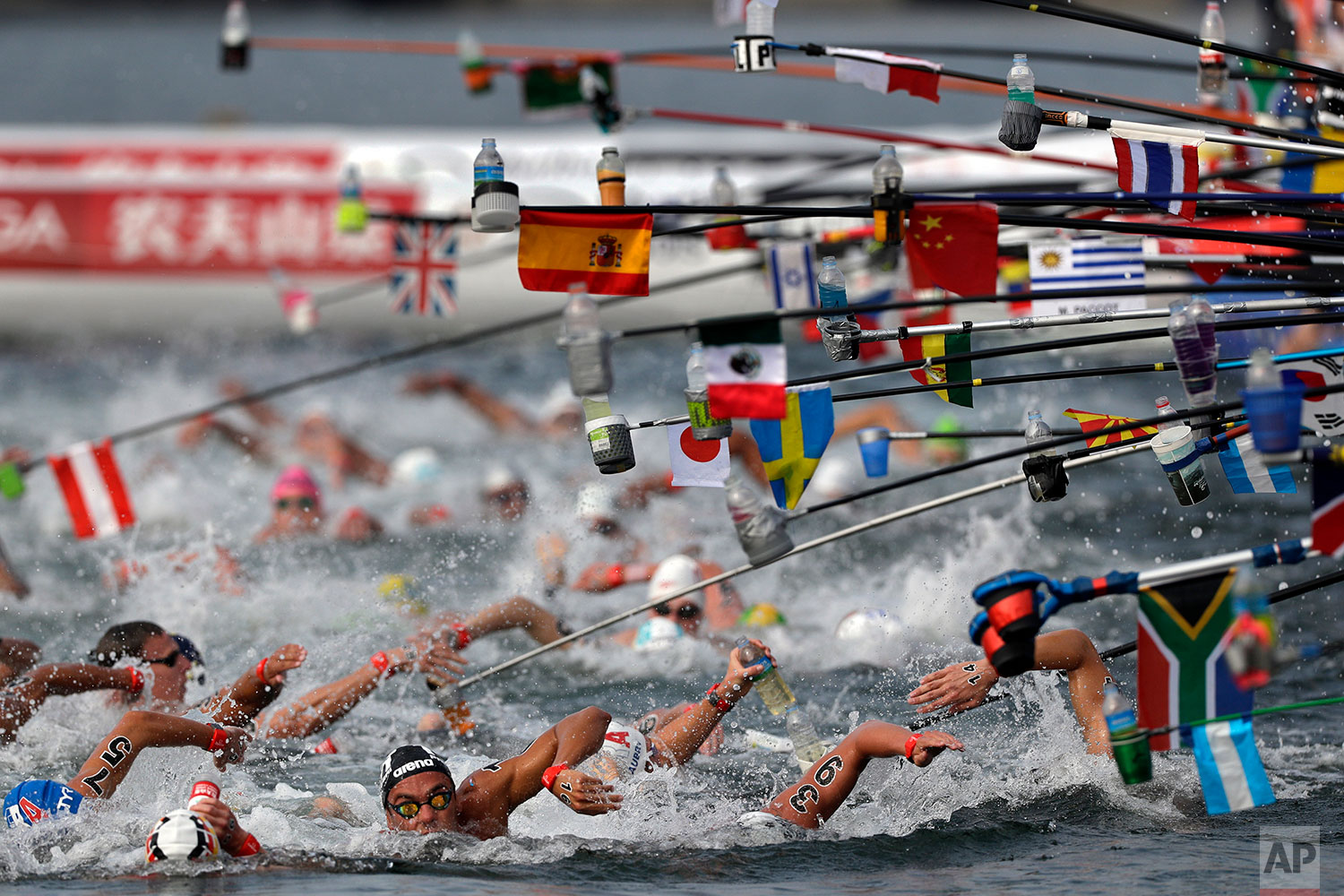 Swimmers reach for drink bottles while competing in the men's 10km open water swim at the World Swimming Championships in Yeosu, South Korea, Tuesday, July 16, 2019. (AP Photo/Mark Schiefelbein)
