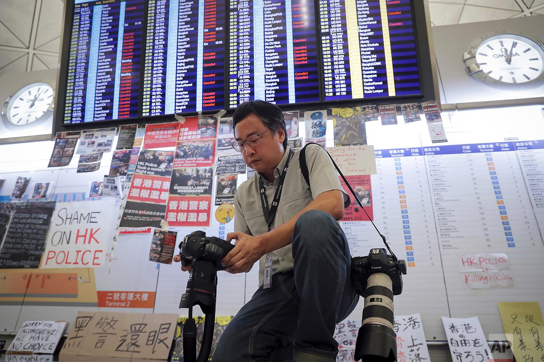 AP photographer Vincent Thian checks the images he shot at the Hong Kong International Airport in Hong Kong, Aug. 12, 2019. (AP Photo/Kin Cheung)