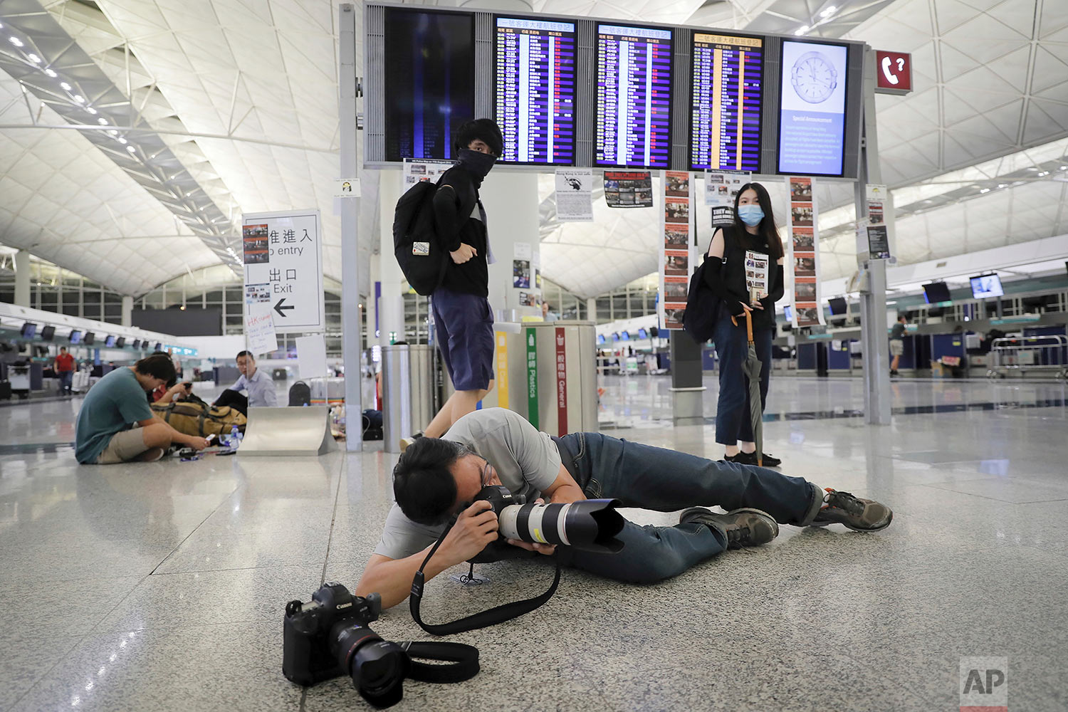 AP photographer Vincent Thian takes photos of stranded travelers after authorities canceled all flights at the Hong Kong International Airport in Hong Kong, Aug. 12, 2019. (AP Photo/Kin Cheung)