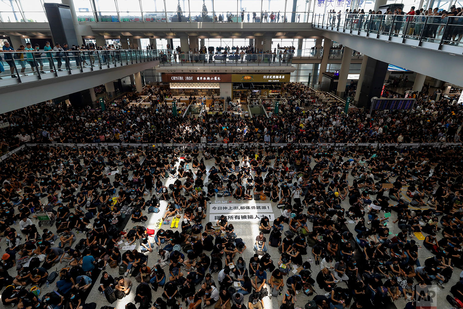 "Protesters surround banners that read: ""Those on the street today are all warriors!"" center top, and ""Release all the detainees!"" during a sit-in rally at the arrival hall of the Hong Kong International airport in Hong Kong, Aug. 12, 2019. (AP Photo/Vincent Thian)"