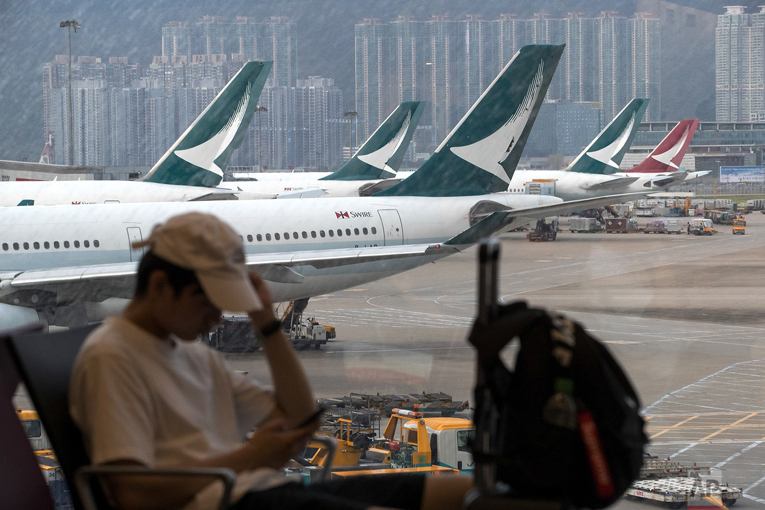 A man checks his smartphone while Cathay Pacific Airways planes park at the Hong Kong International Airport on Monday, Aug. 12, 2019. (AP Photo/Vincent Thian)
