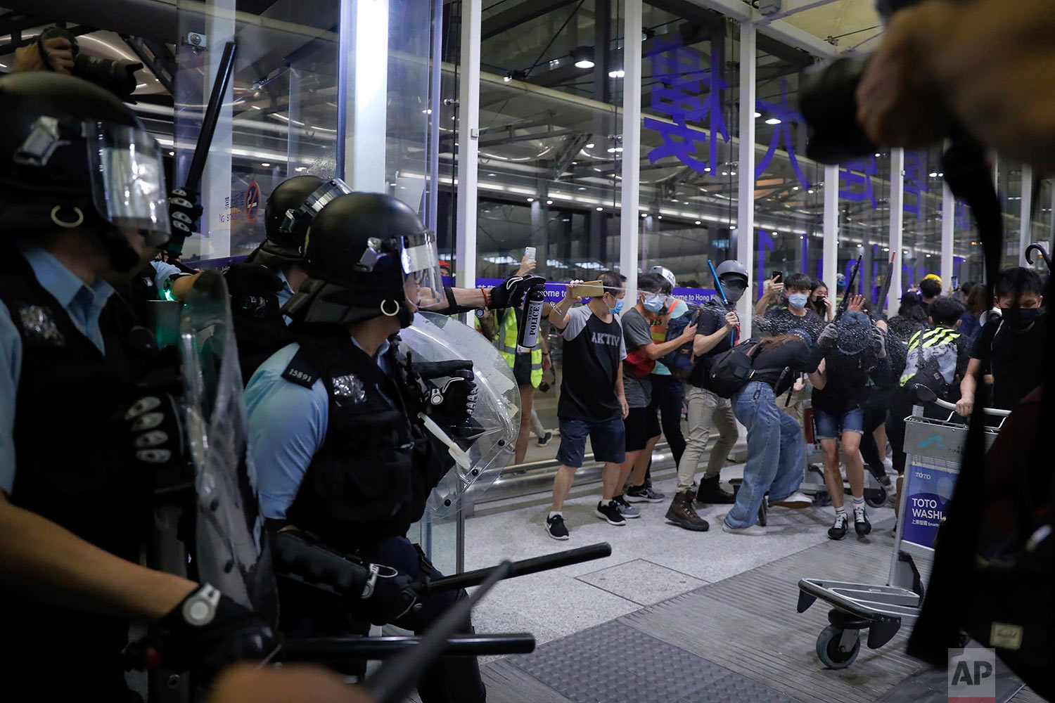 Policemen in riot gears use pepper spray on the protesters during a demonstration at the Airport in Hong Kong, Tuesday, Aug. 13, 2019. (AP Photo/Kin Cheung)