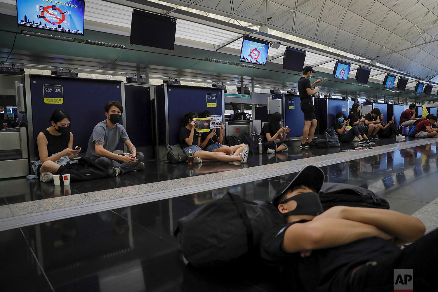 Protesters gather at the closed check-in counters at the Hong Kong International Airport, Aug. 12, 2019. (AP Photo/Kin Cheung)