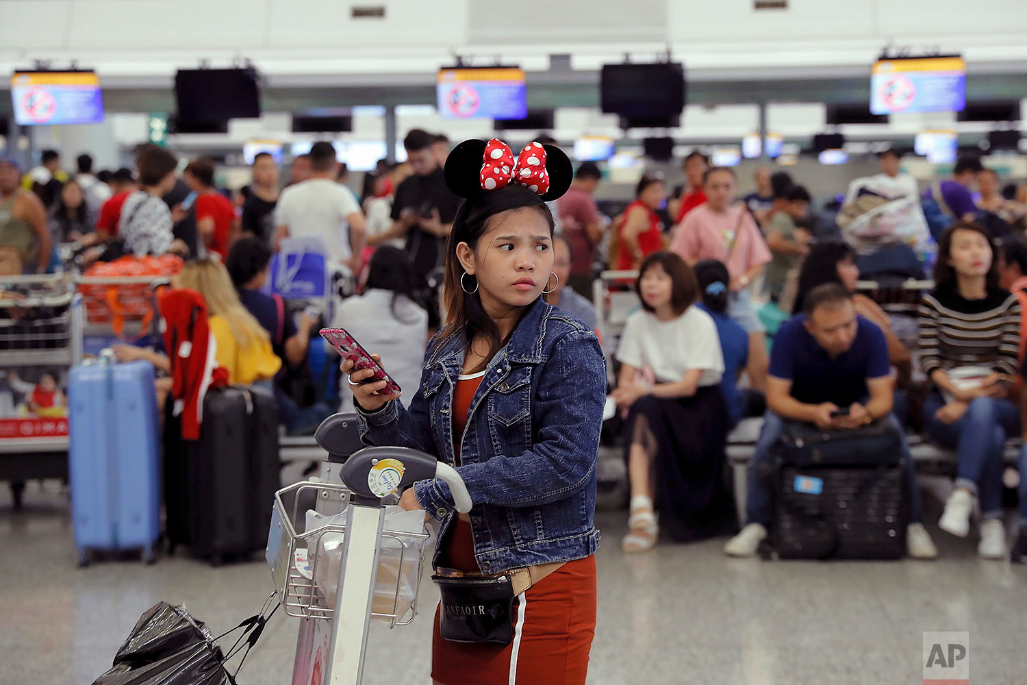 A woman wearing Minnie Mouse headgear looks on as stranded travelers gather near the closed check-in counters at the Airport in Hong Kong, Tuesday, Aug. 13, 2019. (AP Photo/Kin Cheung)