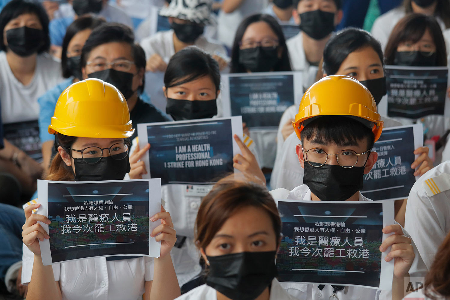 Medical staff take part in a protest against police brutality on the protesters, at a hospital in Hong Kong, Tuesday, Aug. 13, 2019. (AP Photo/Kin Cheung)