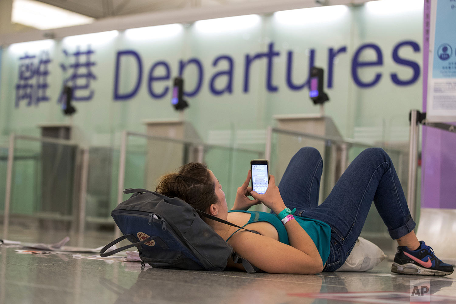 A traveler leans on her bag while browsing her smartphone at the departure hall of the Hong Kong International airport on Aug. 12, 2019. (AP Photo/Vincent Thian)