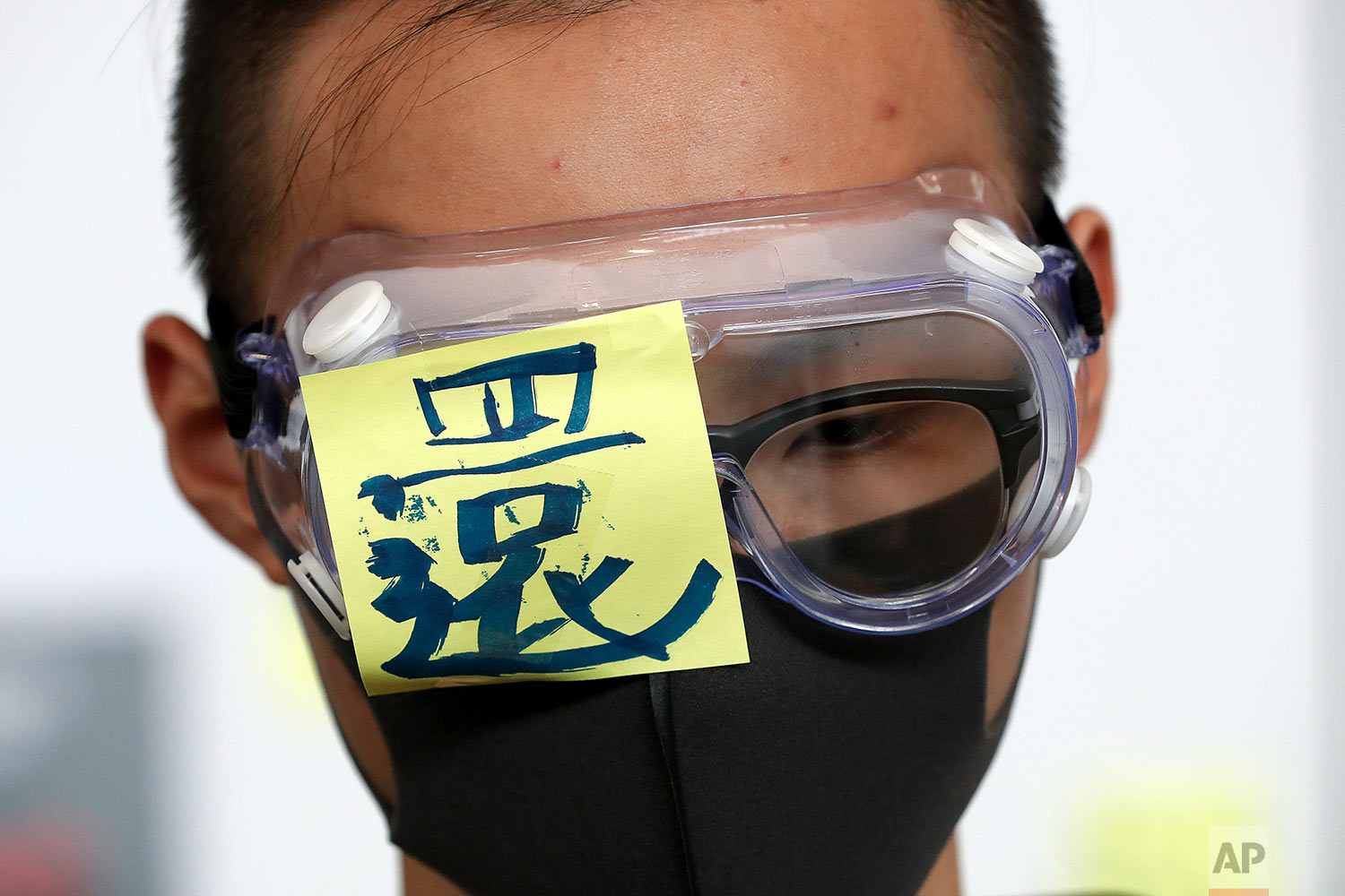 "A protester wears a goggle with a word ""Return"" during a protest at the arrival hall of the Hong Kong International Airport in Hong Kong Monday, Aug. 12, 2019. (AP Photo/Vincent Thian)"