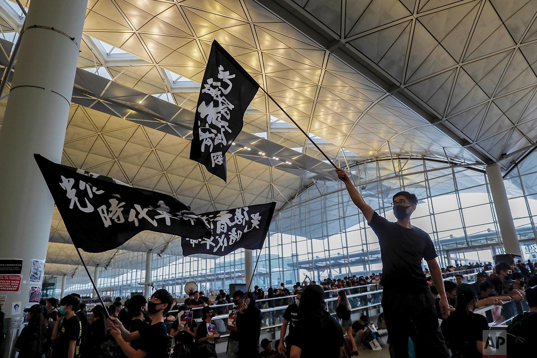 Protesters wave flags at the Hong Kong International Airport, Monday, Aug. 12, 2019. (AP Photo/Kin Cheung)