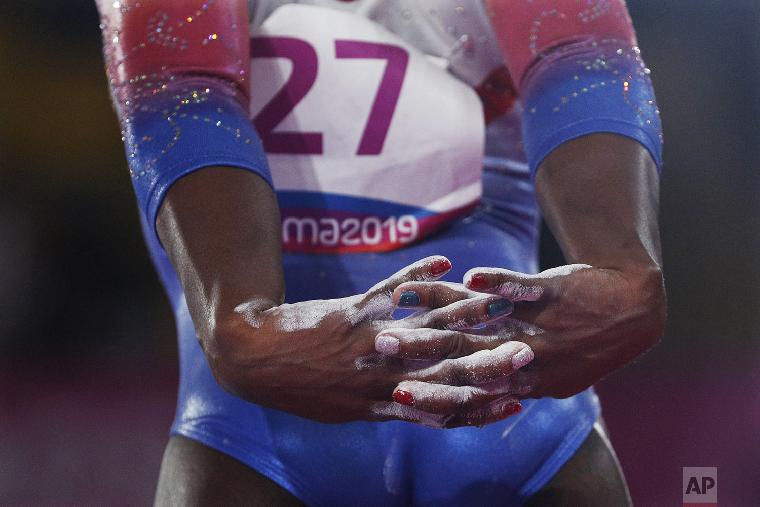 Yesenia Saskia Ferrera, of Cuba, stretches her arms behind her back as she prepares to compete on beam in the women's gymnastics qualification and team final at the Pan American Games in Lima, Peru, Saturday, July 27, 2019. (AP Photo/Rebecca Blackwell)
