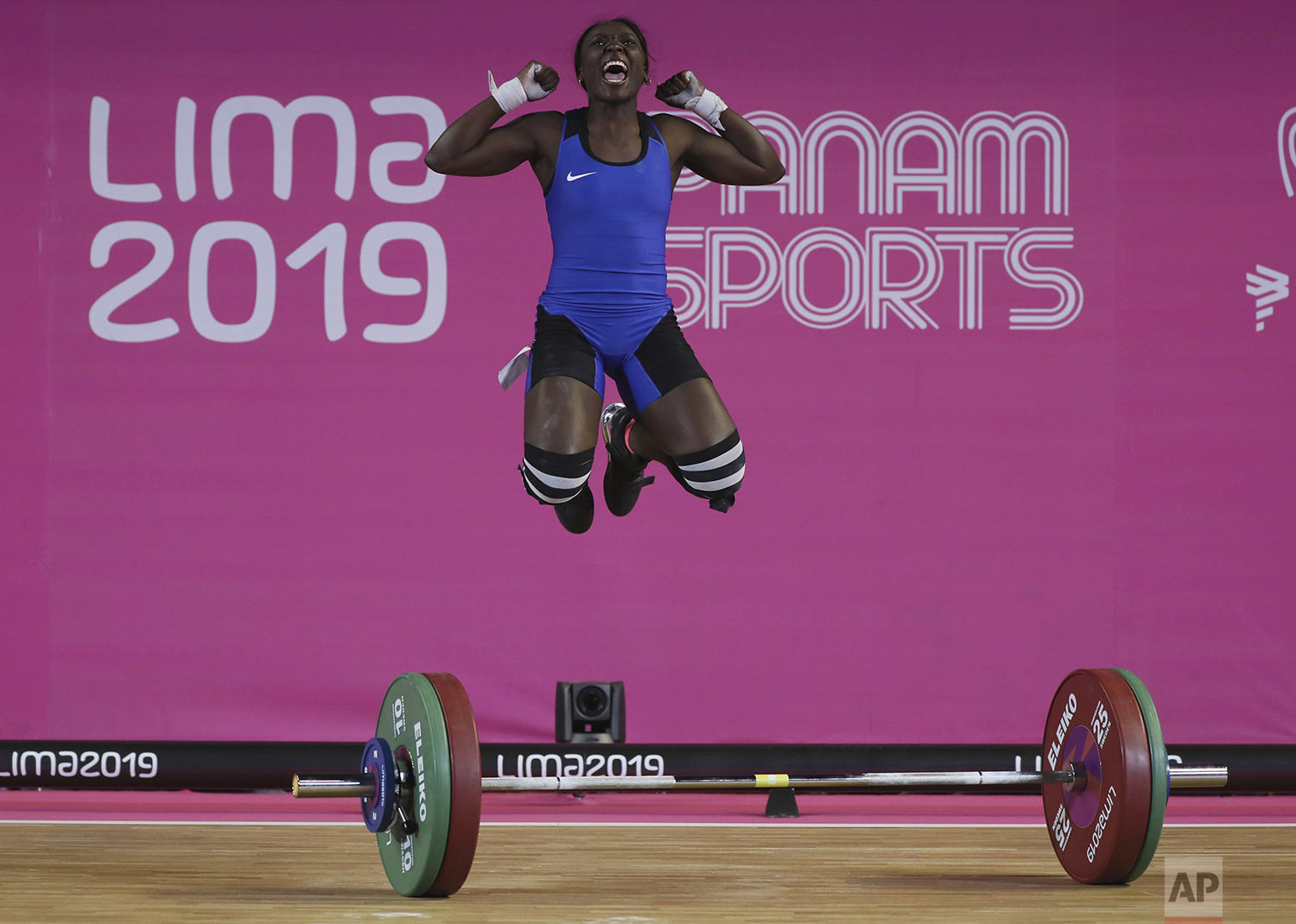 Yenni Sinisterra of Colombia celebrates after lifting 94 kg during the snatch women's weightlifting 55 kg event at the Pan American Games in Lima, Peru, Sunday, July 28, 2019. (AP Photo/Fernando Llano)