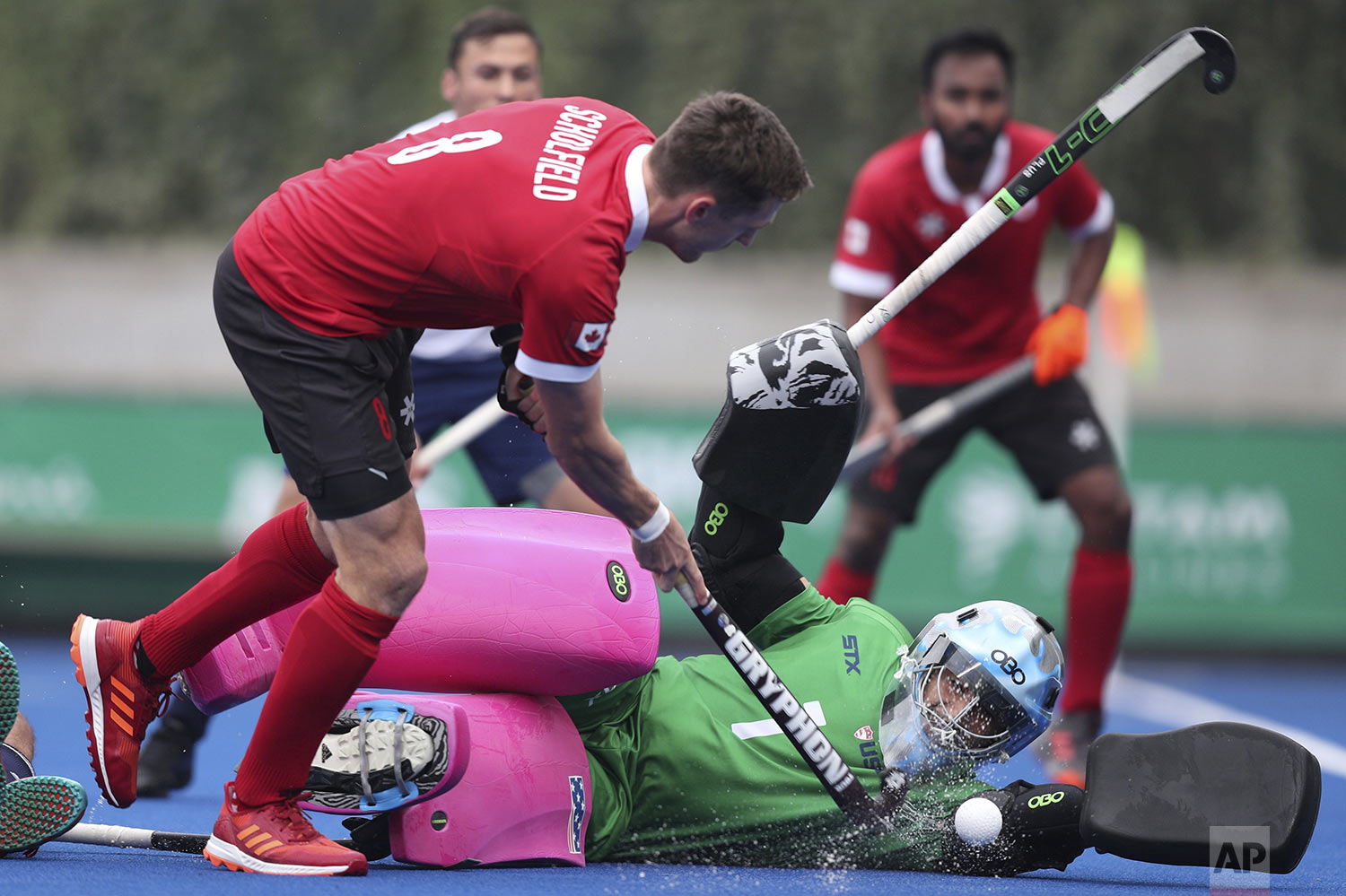 Goalkeeper Jonathan Klages of United States blocks a shot by Oliver Scholfield of Canada, left, during the field hockey men's preliminaries group B match, at the Pan American Games in Lima, Peru, Thursday, Aug. 1, 2019. (AP Photo/Martin Mejia)