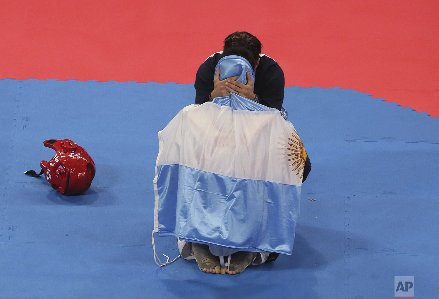 Argentina's Lucas Guzman is draped in his nation's flag as he's congratulated by his coach after winning the gold in the men's under 58kg Taekwondo event, after Guzman defeated Brandon Plaza, of Mexico, at the Pan American Games in Lima, Peru, Saturday, July 27, 2019. (AP Photo/Fernando Llano)