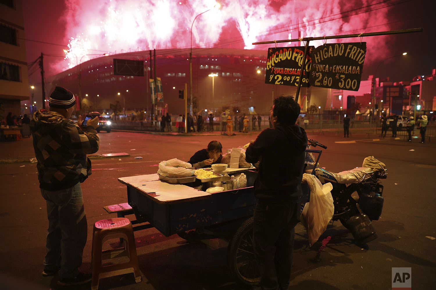 Vendors at a food stand watch fireworks exploding over the National stadium during the closing ceremony of the Pan American Games in Lima, Peru, Sunday, Aug. 11, 2019. (AP Photo/Rodrigo Abd)