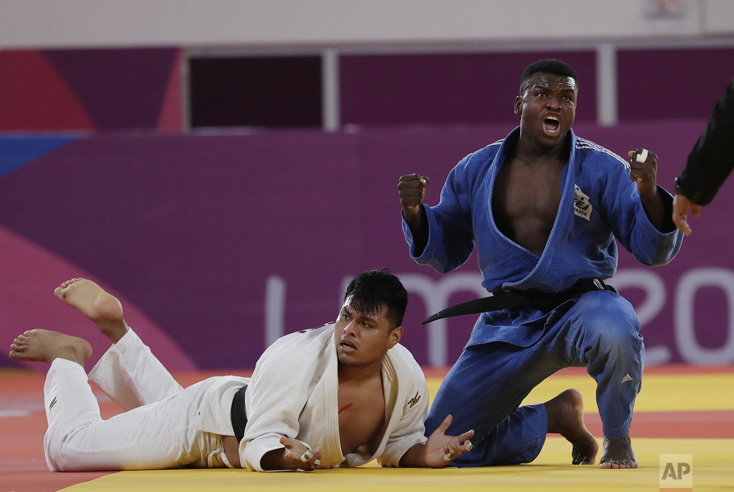 Junior Angulo of Ecuador, right, celebrates after beating Jose Arroyo of Peru in the men's - 100kg bronze medal judo match at the Pan American Games in Lima Peru, Sunday, Aug.11, 2019. (AP Photo/Silvia Izquierdo)