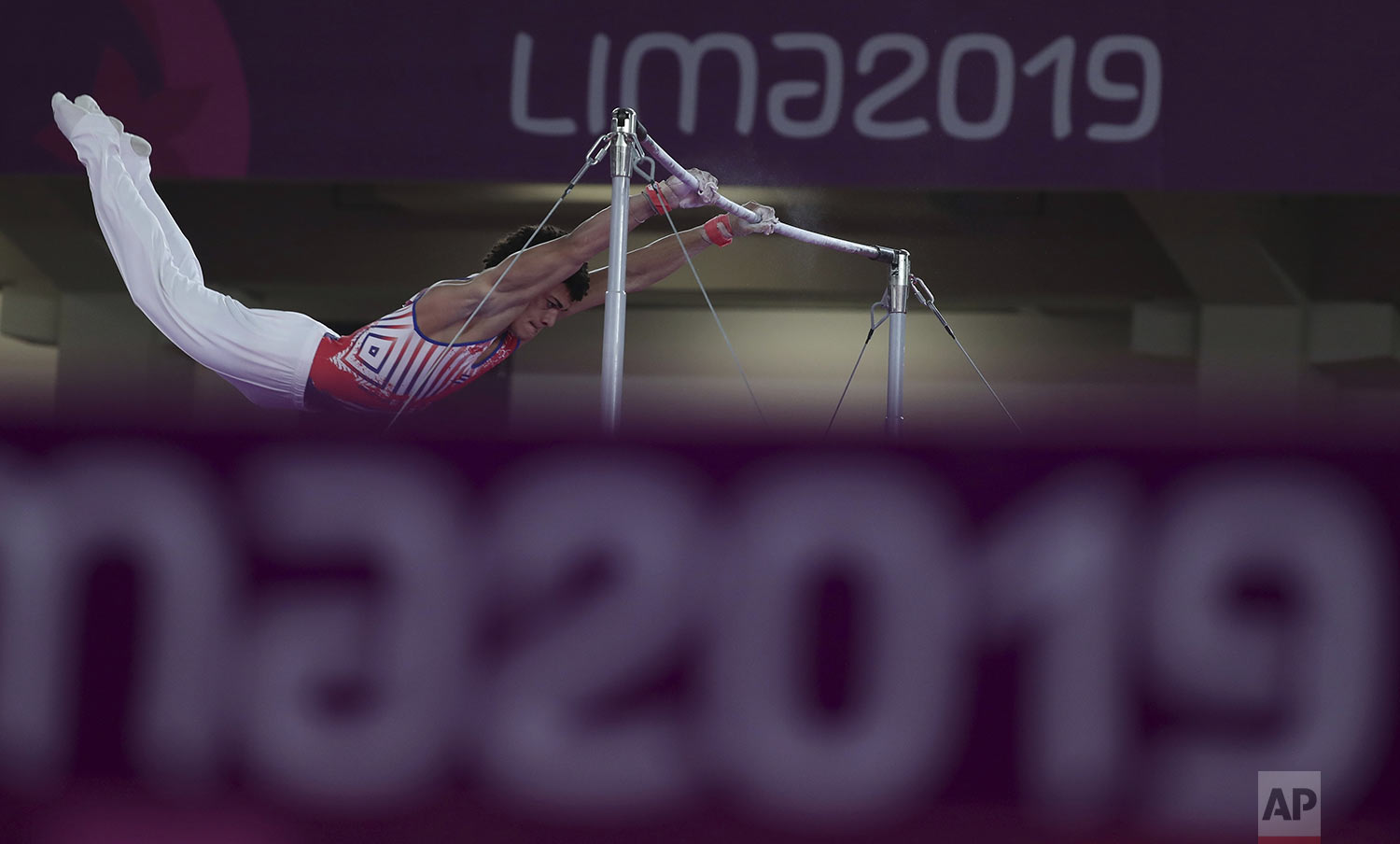 Huber Godoy of Cuba competes on the horizontal bar in the men's artistic gymnastics apparatus at the Pan American Games in Lima, Peru, Wednesday, July 31, 2019. Godoy won the bronze medal. (AP Photo/Fernando Vergara)