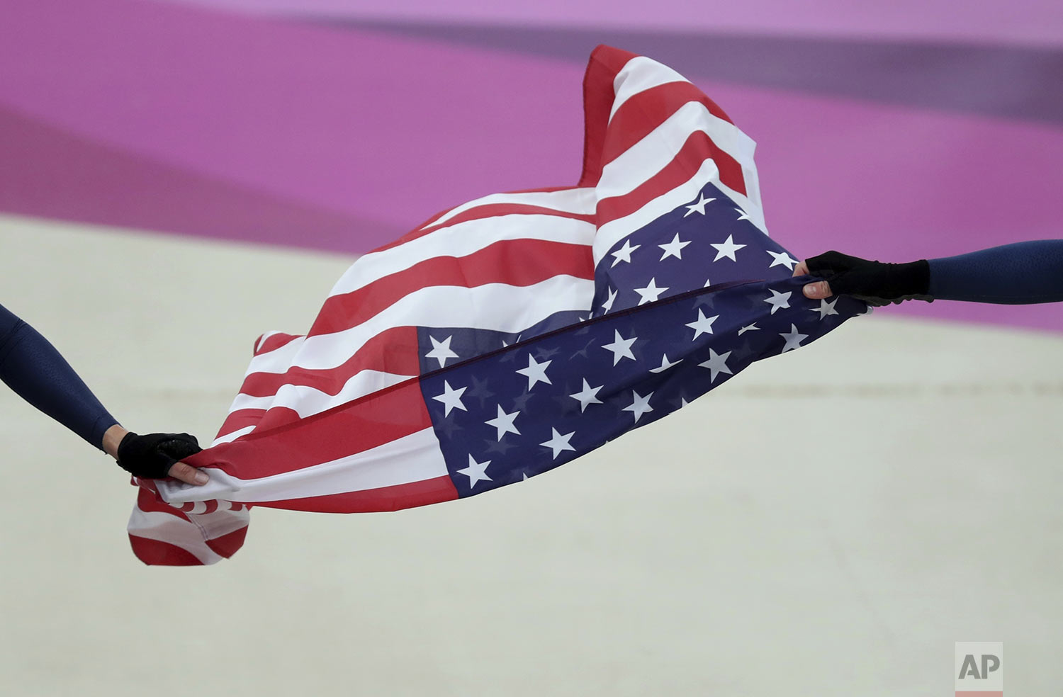 Kimberly Geist, left, and Christina Birch, of the United States, hold their nation's flag to celebrate winning the gold in women's Madison track cycling at the Pan American Games in Lima, Peru, Sunday, Aug. 4, 2019. (AP Photo/Fernando Vergara)
