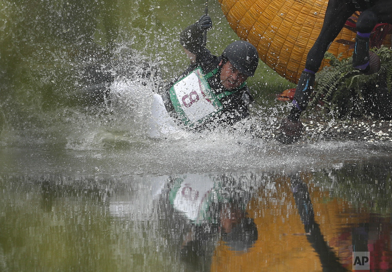 Colombia's Mauricio Bermudez lands in the water after being thrown when his horse Fernhill Nightshift tripped while crossing a jump, in the cross country discipline of equestrian eventing at the Pan American Games in Lima, Peru, Saturday, Aug. 3, 2019. (AP Photo/Rebecca Blackwell)