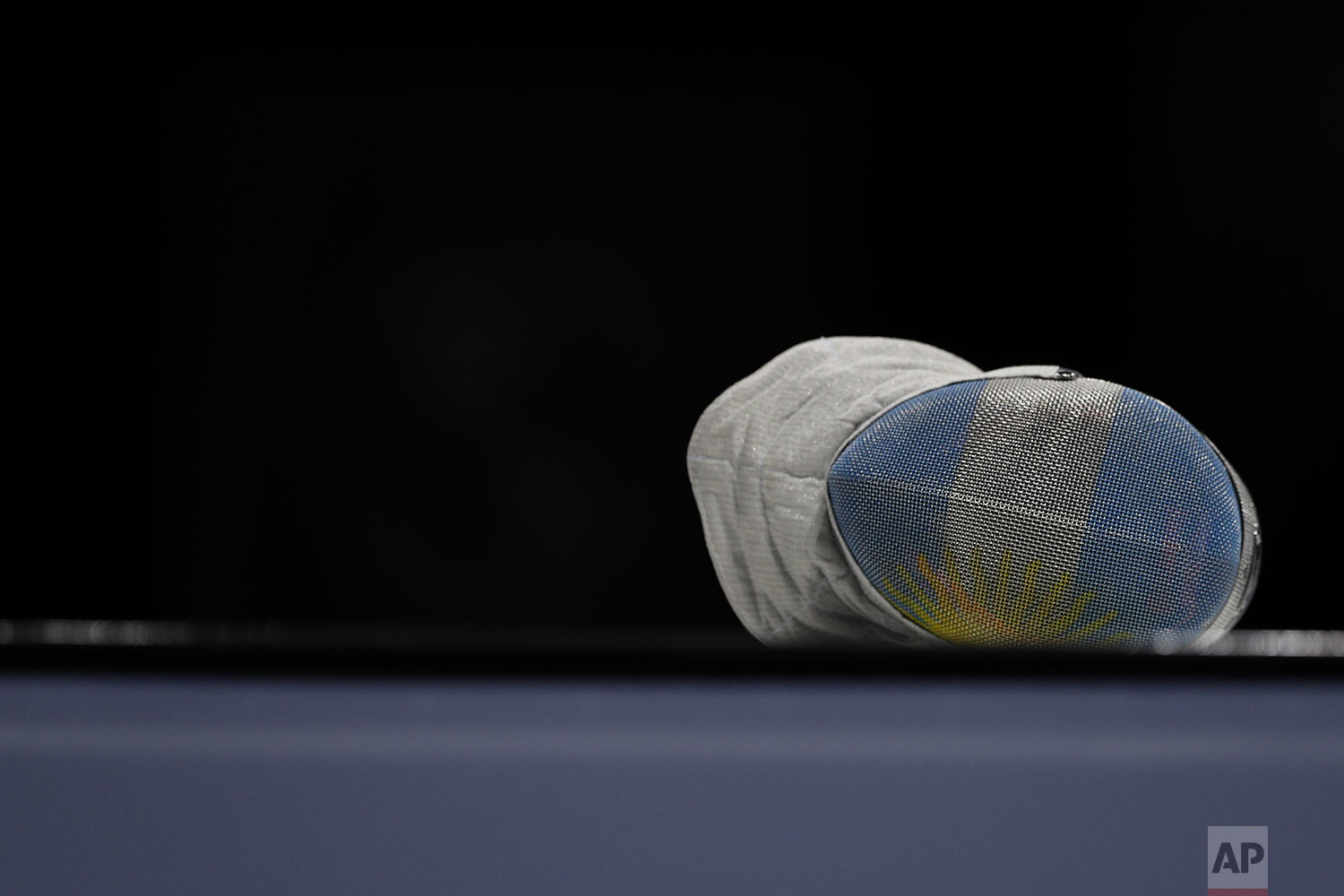 The mask of Argentina's Maria Perez lies on the fencing platform during a pause in her women's sabre individual fencing semifinal against Venezuela's Alejandra Benitez at the Pan American Games in Lima, Peru, Tuesday, Aug. 6, 2019. (AP Photo/Rebecca Blackwell)