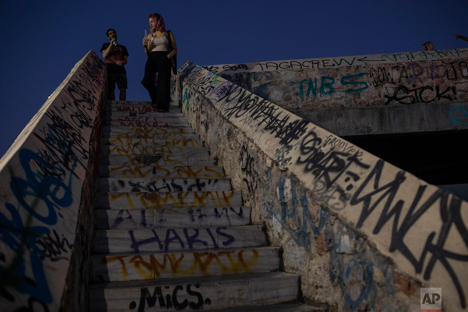 People stand on a graffiti-covered pedestrian bridge over railway lines beside the ancient Kerameikos cemetery in central Athens, July 26, 2019. (AP Photo/Petros Giannakouris)