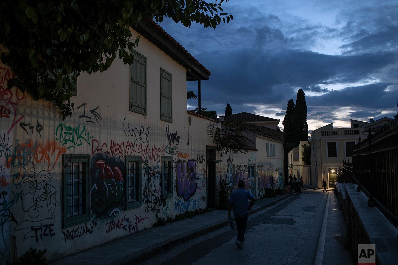 A man walks next to graffiti covered houses in Plaka district, Athens, July 3, 2019. (AP Photo/Petros Giannakouris)