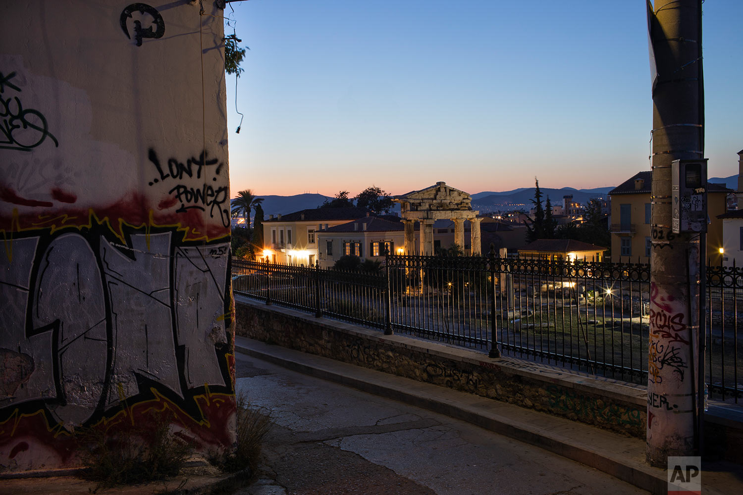 The facade of a building and an electricity pole are covered with graffiti in front the Gate of the ancient Roman agora in Plaka district of Athens, July 7, 2019. (AP Photo/Petros Giannakouris)