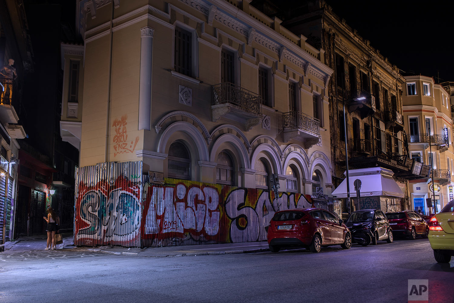 The fence of a renovated building and part of the wall are defaced with graffiti in Monastiraki district, central Athens, July 7, 2019. (AP Photo/Petros Giannakouris)