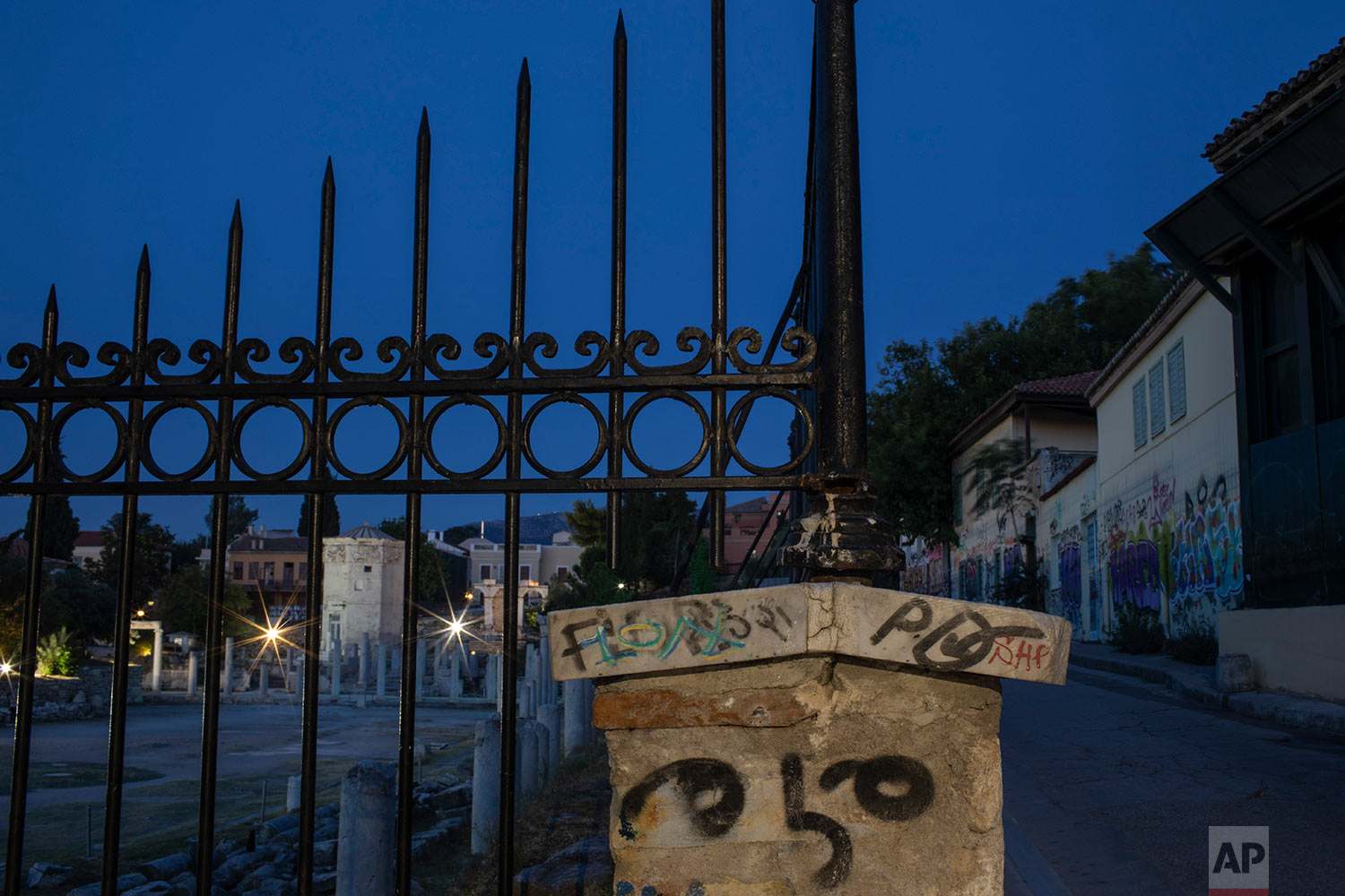 In this Monday, July 22, 2019 photo, a fence and buildings are covered with graffiti outside the ancient Roman agora in Plaka district of Athens. (AP Photo/Petros Giannakouris)