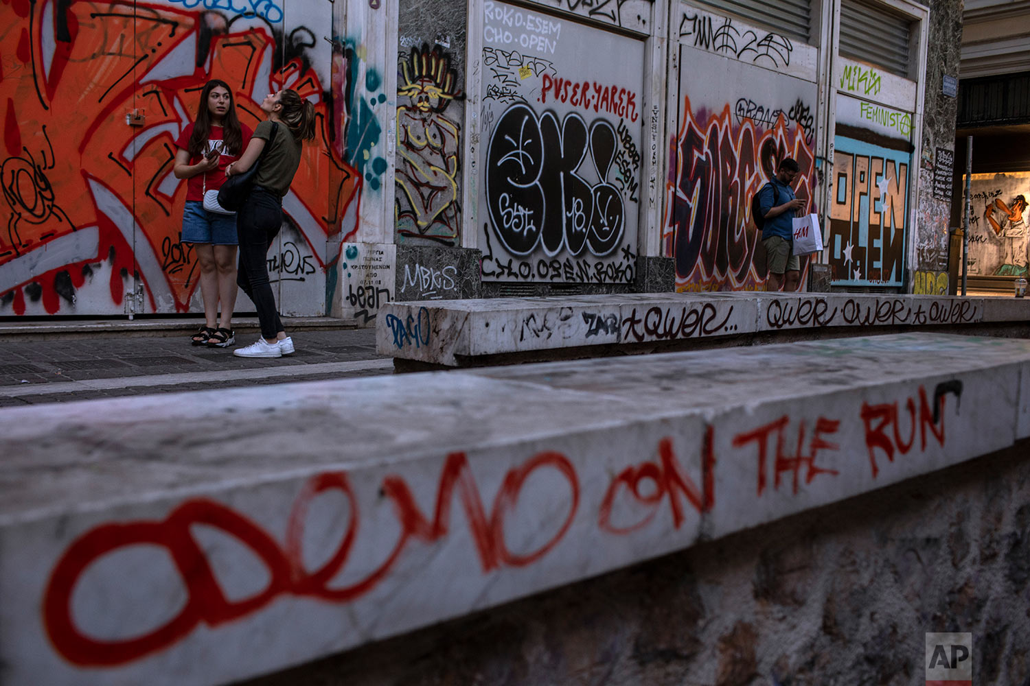 A marble-topped wall round the 11th Century AD Panagia Kapnikarea church and a shop that has been closed for months are covered with graffiti in Athens' Ermou main shopping street, July 26, 2019. (AP Photo/Petros Giannakouris)