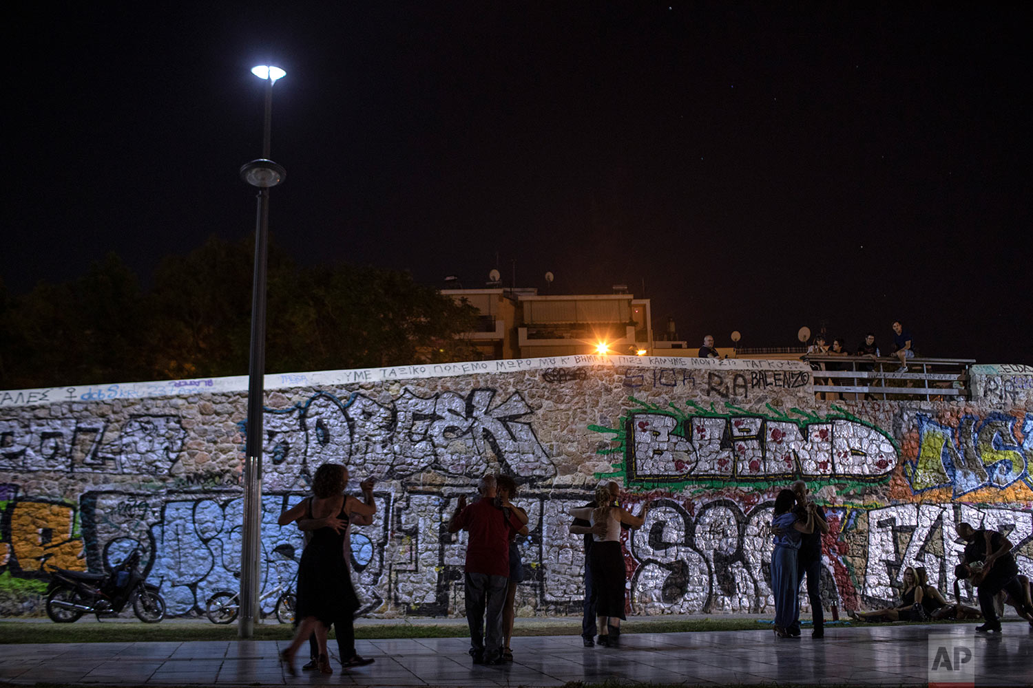 People dance tango against a stone bridge covered with graffiti in Thission district of Athens, July 26, 2019. (AP Photo/Petros Giannakouris)