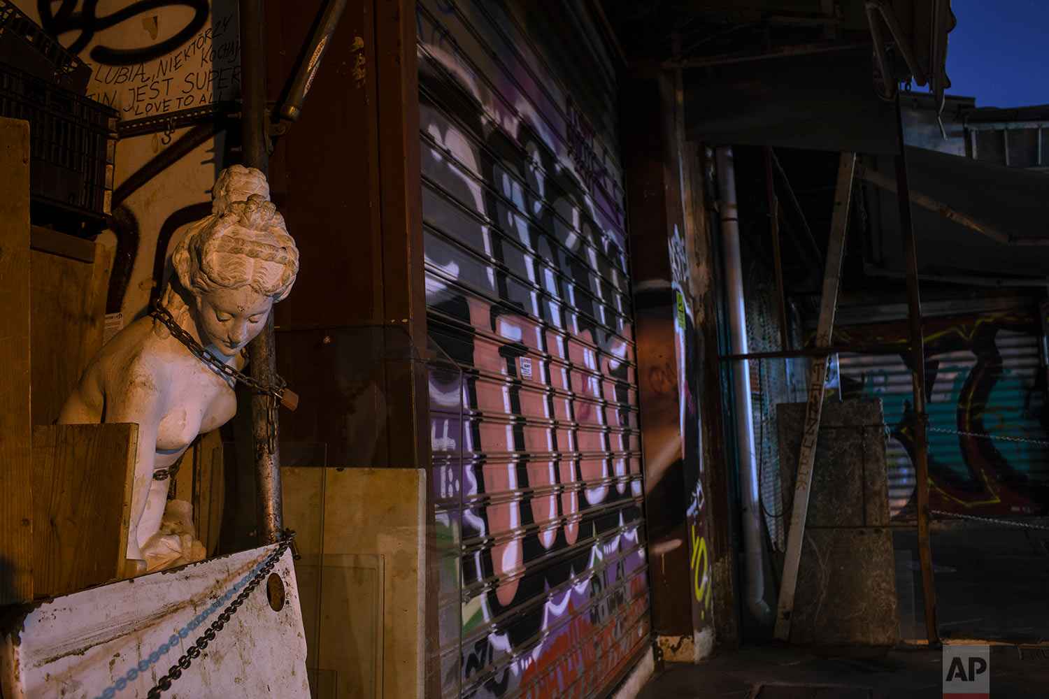 A modern copy of a statue of Aphrodite, ancient Greek Goddess of beauty, is chained to a wall outside a closed antique shop as shutters of other shops are covered with graffiti in Monastiraki district, central Athens, July 22, 2019. (AP Photo/Petros Giannakouris)