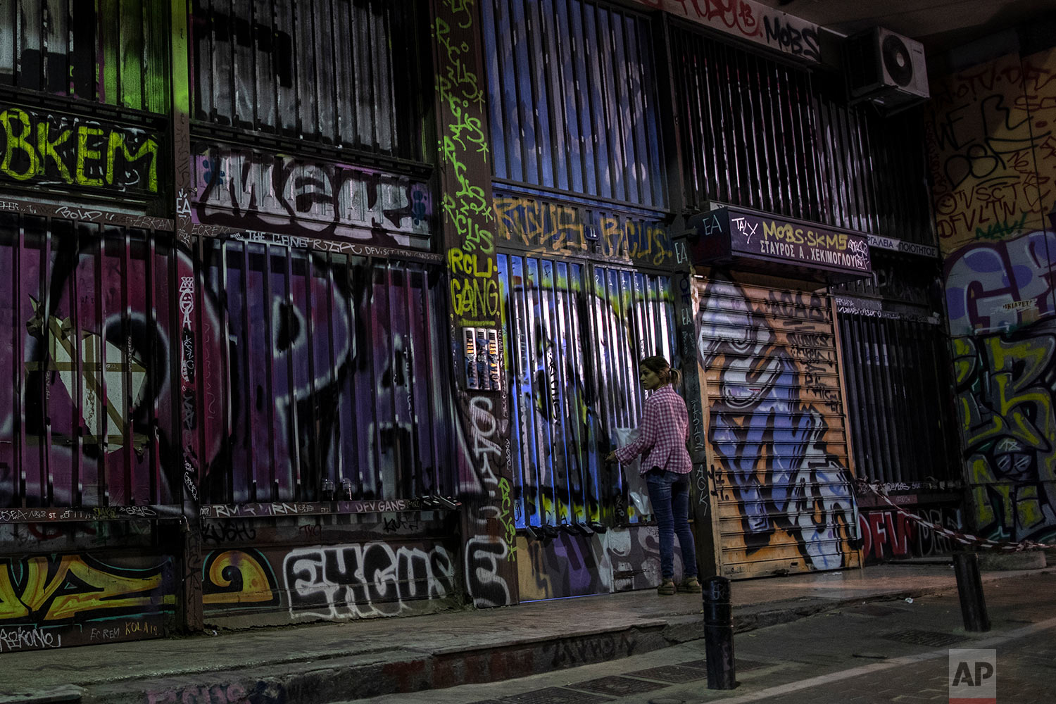 A woman opens with her key the entrance of a building which is covered with graffiti in Psiri district, central Athens, July 25, 2019. (AP Photo/Petros Giannakouris)