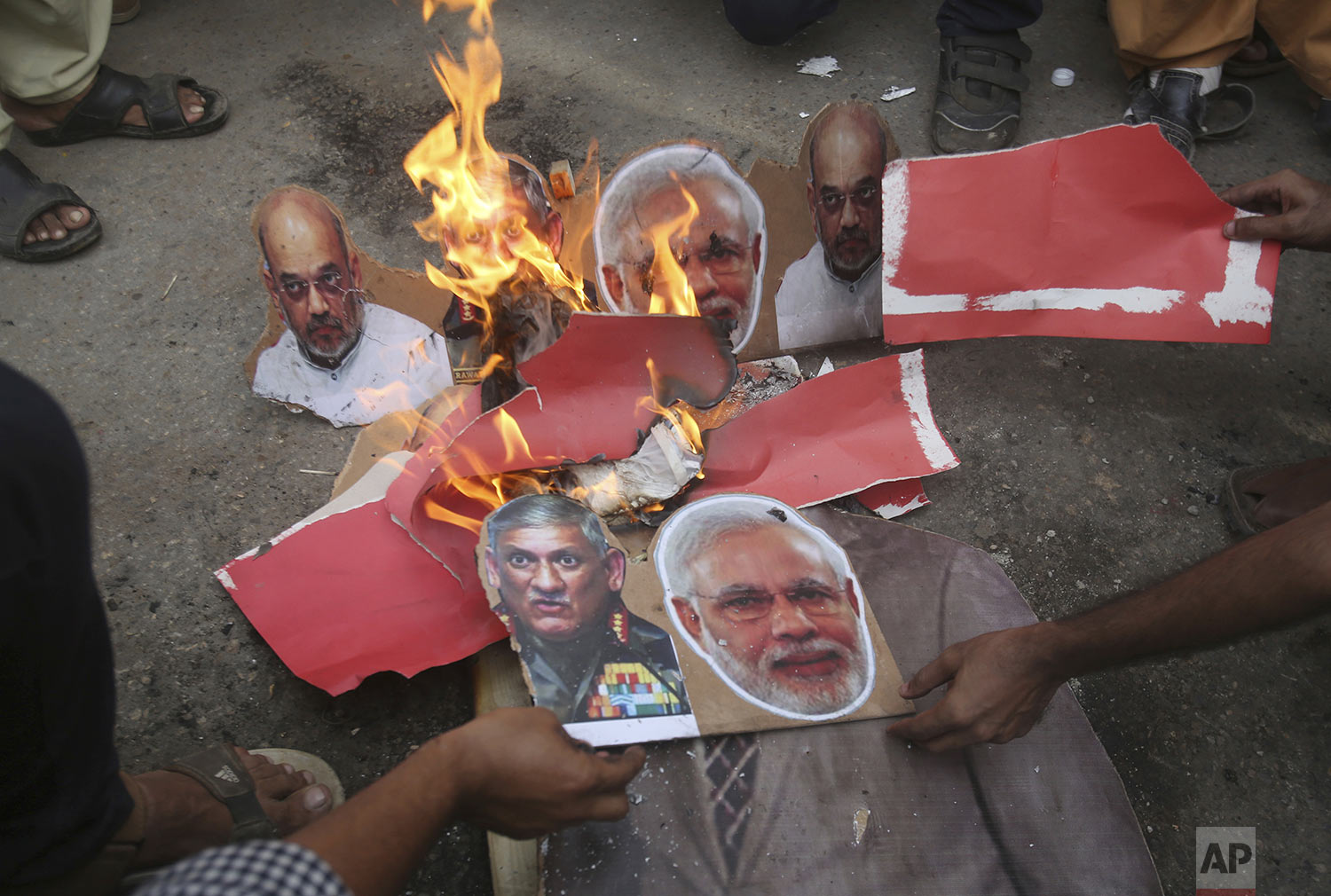 Pakistani protesters burn posters of Indian leaders during a protest in Karachi, Pakistan, Friday, Aug. 9, 2019. (AP Photo/Fareed Khan)