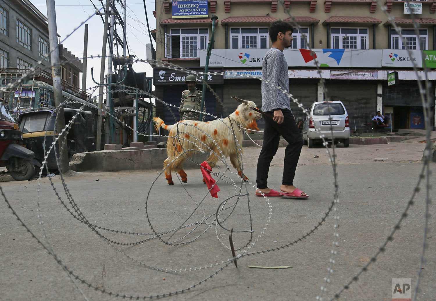 A Kashmiri Muslim civilian crosses a check point ahead of Eid -ul Adha during curfew in Srinagar, Indian controlled Kashmiri, Friday, Aug. 9, 2019. (AP Photo/Mukhtar Khan)